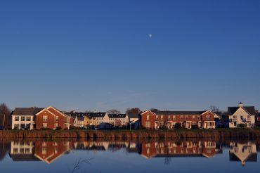 Hendrix Road apartments and townhouses overlooking the pond at dusk.