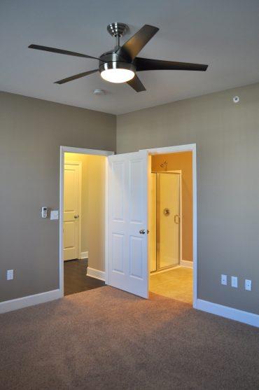 Villa master bedrooms showcase a modern ceiling fan and a walk-in shower in the en suite.