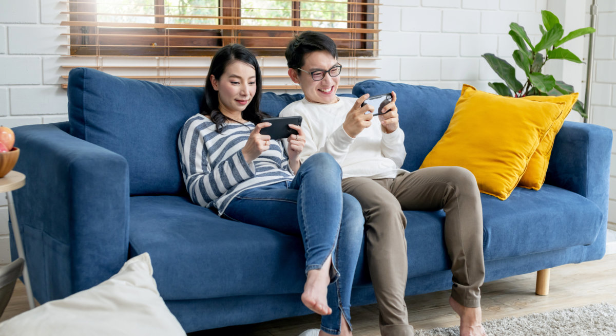 Couple seated on sofa in there apartment using their smartphones