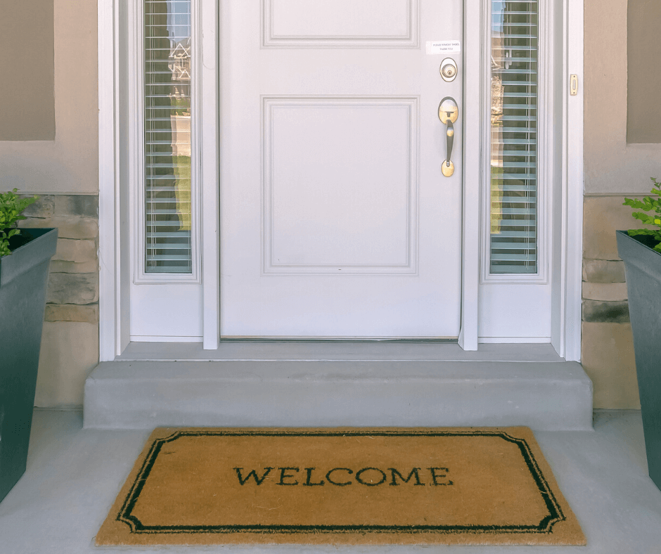 Front door with welcome mat and potted plants