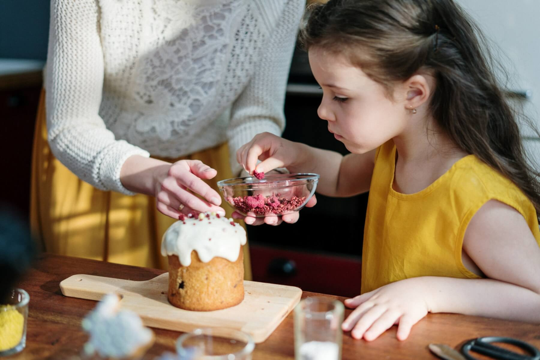 Young girl sprinkling toppings on a dessert with her mother
