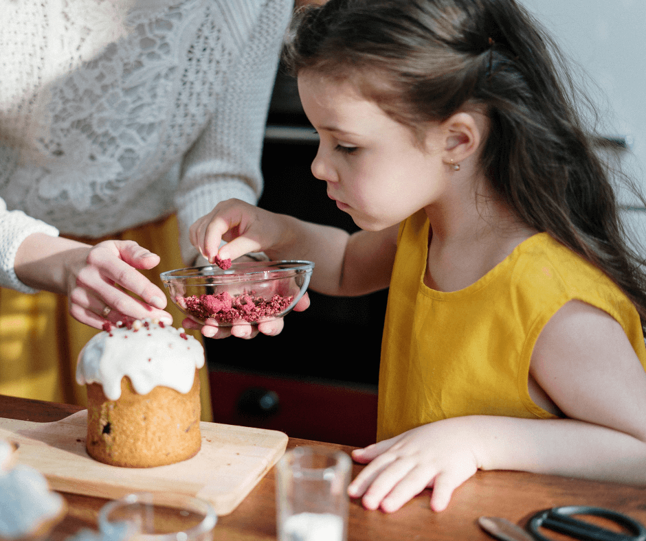 Young girl sprinkling toppings on a desert with her mother