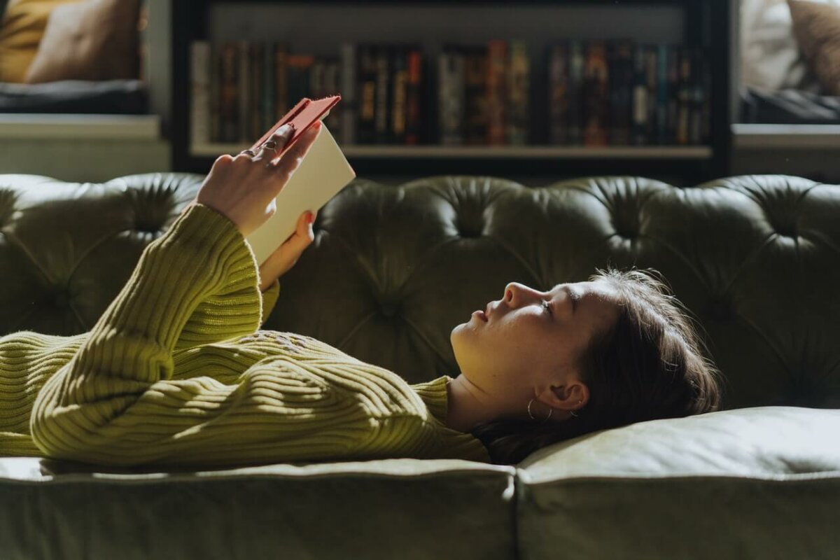 Woman laying on a sofa reading a book. Image credit: cottonbro