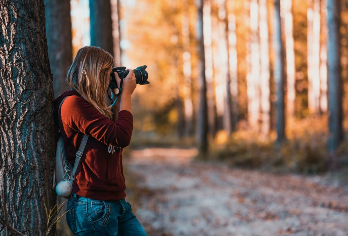 Photo of woman taking a photo with a DSLR camera in a forest. Photo credit: David Bartus