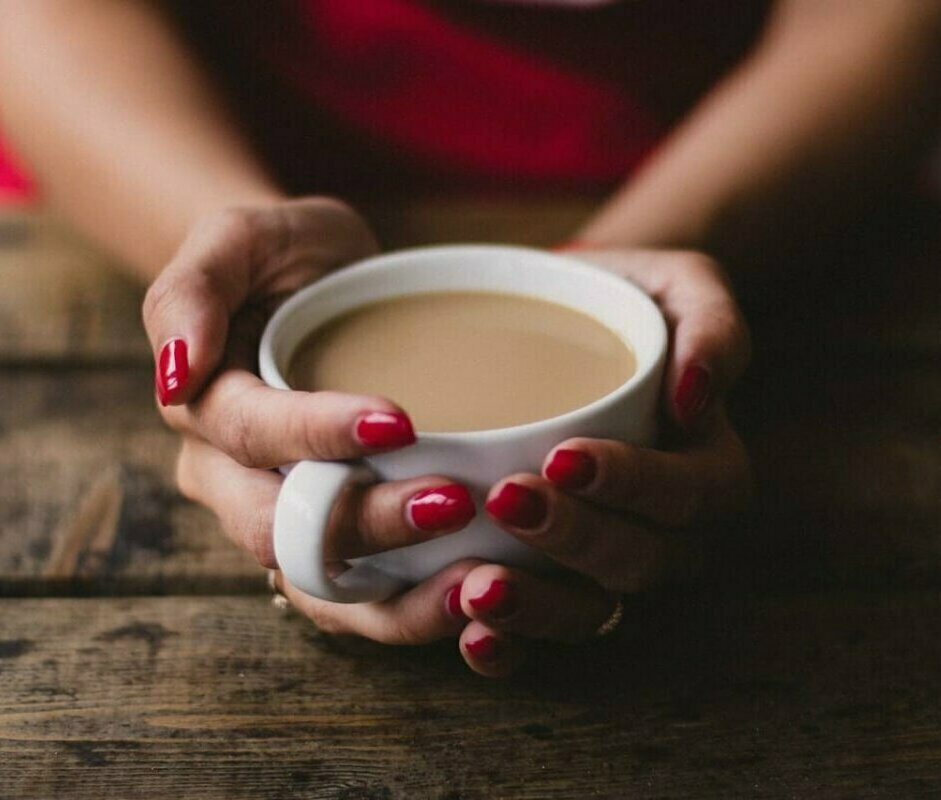 Woman holding a cup of coffee. Image credit Kristina Paukshtite