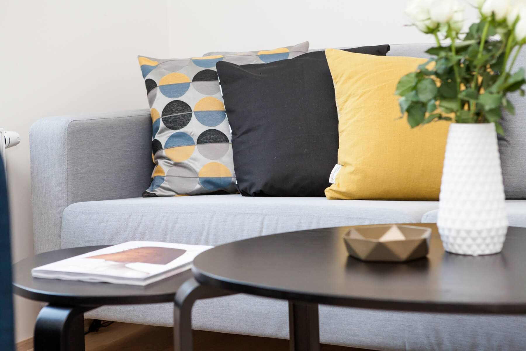 Colorful pillows on a living room couch. Photo credit: Terje Sollie