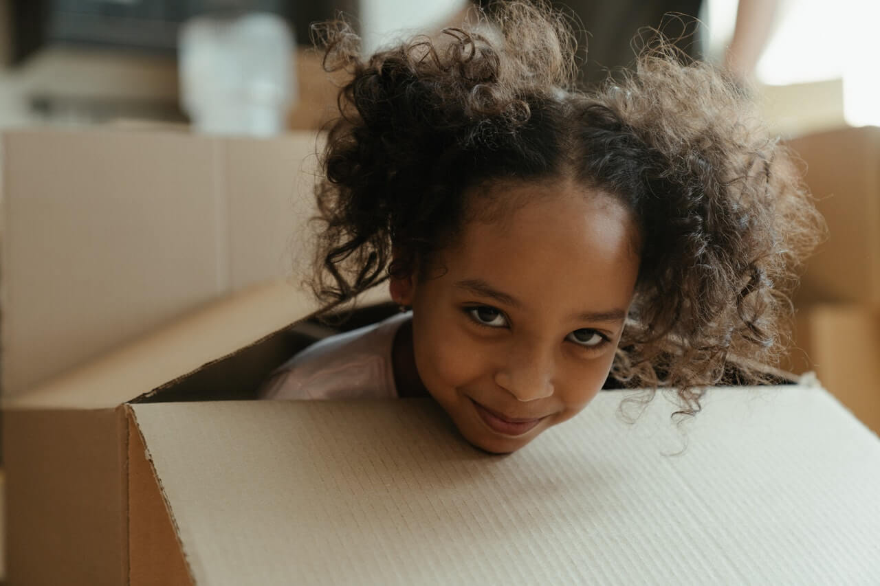 Young girl peeking out of a large cardboard box. Photo credit: Cottonbro