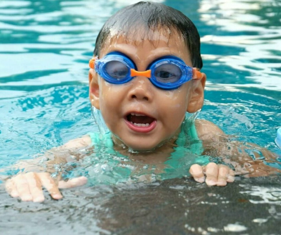 Young boy wearing swimming goggles in a pool. Image credit Porapak Apichodilok